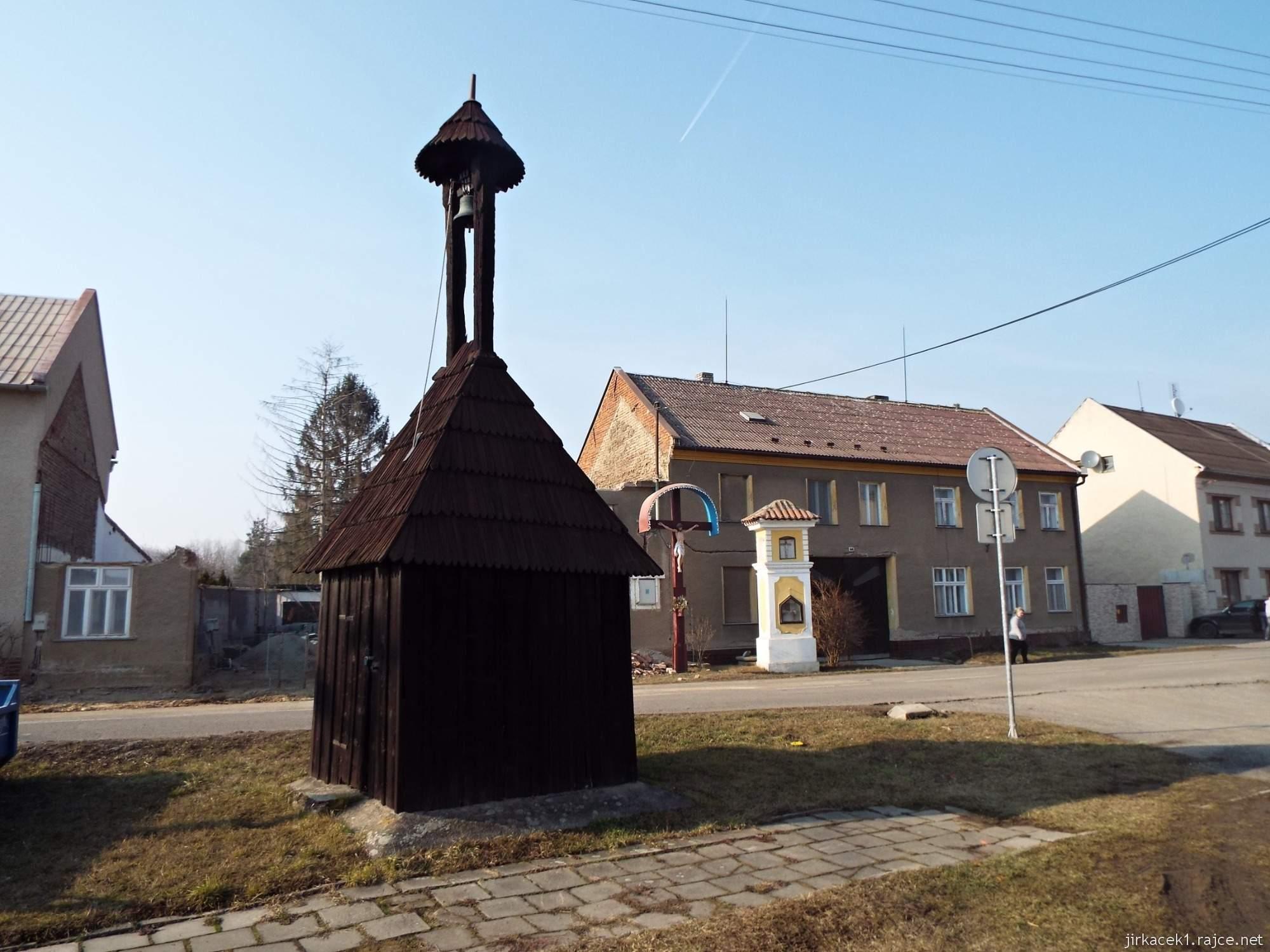 Lhota nad Moravou - náves - dřevěná zvonička a za ní Boží muka